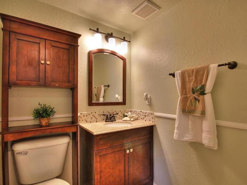 Small craftsman style bathroom with over toilet storage cabinet