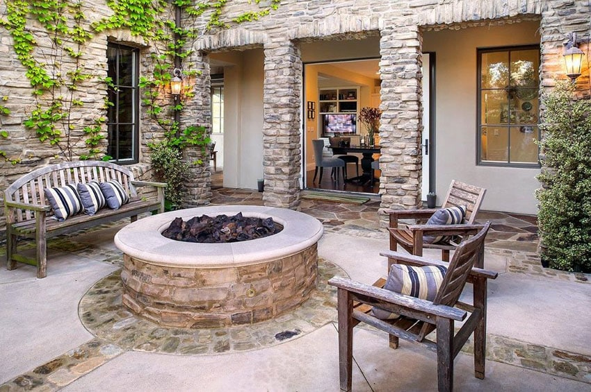 Stone and concrete patio with round fire pit and stacked stone veneer home exterior