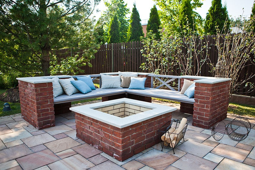 Stone tile patio with brick firepit and brick bench in backyard