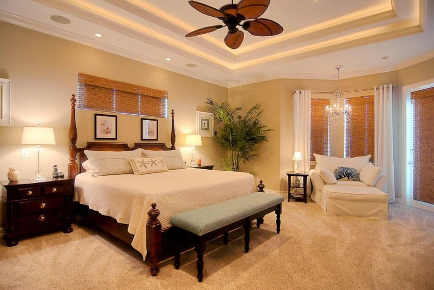 Tan bedroom with matching carpet and tray ceiling with fan