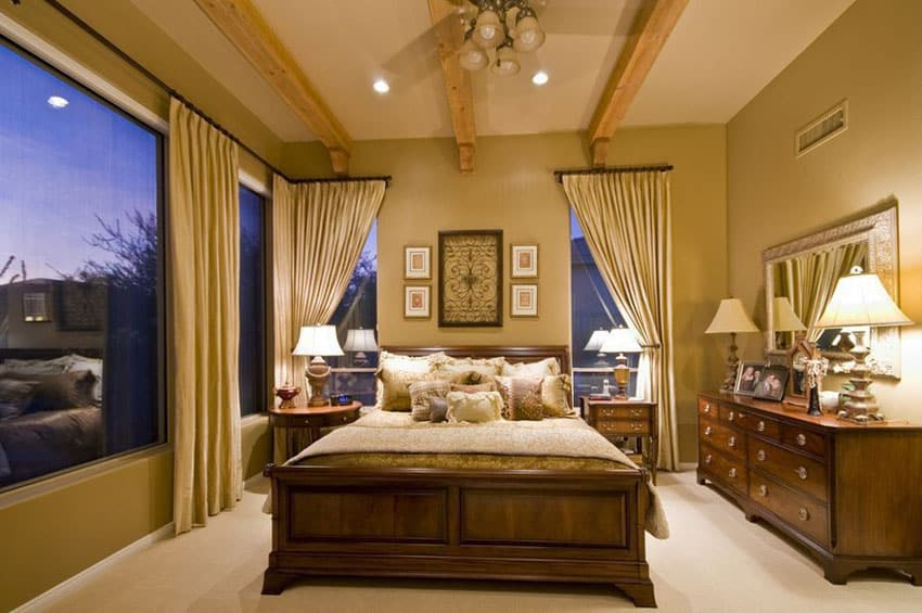 Tan color bedroom with wood furniture and exposed beam ceiling