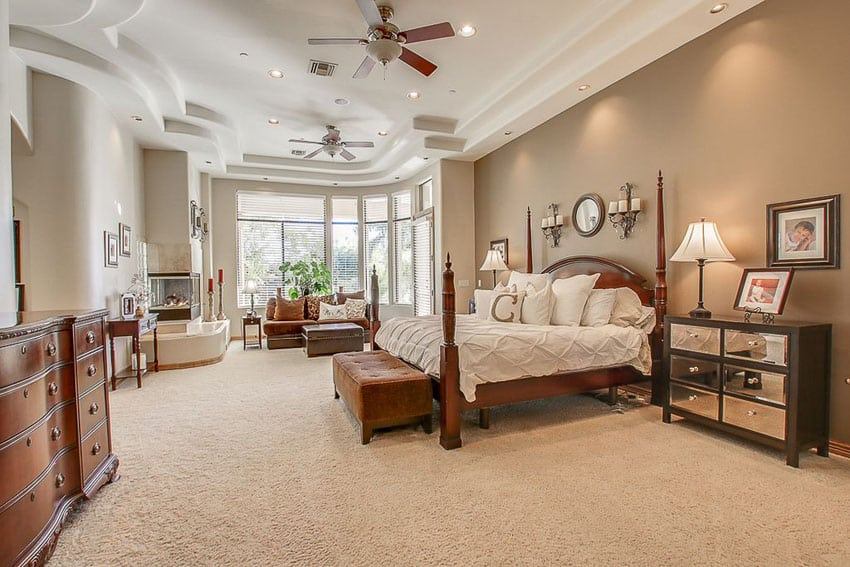 Tan color master bedroom with wood four post bed and fireplace