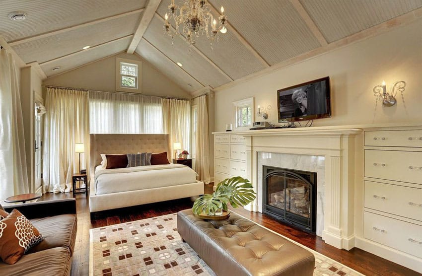 Tan contemporary master bedroom with vaulted ceiling fireplace and tufted bed