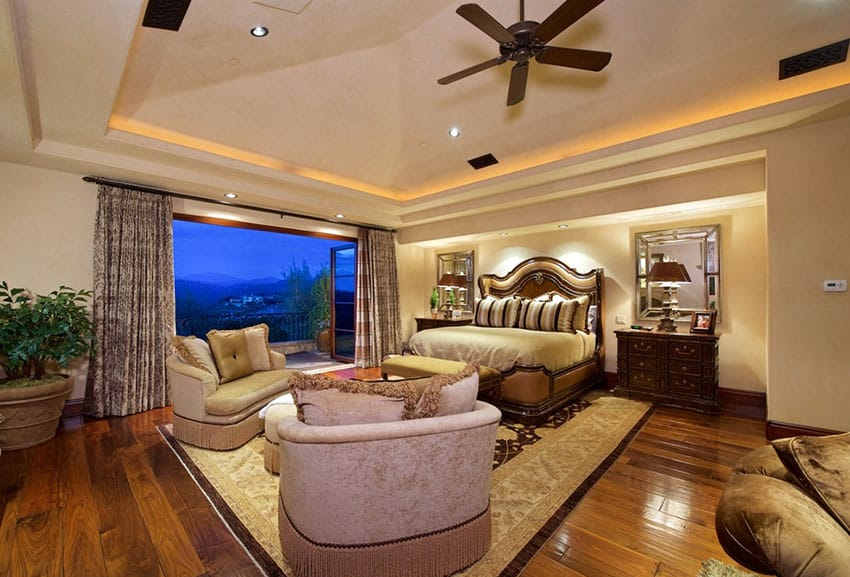 Tan luxury master bedroom with wood floors and outdoor balcony
