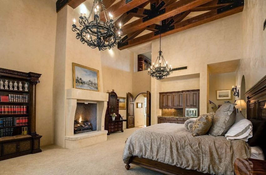 Tan Mediterranean bedroom with fireplace exposed beams and vaulted ceiling