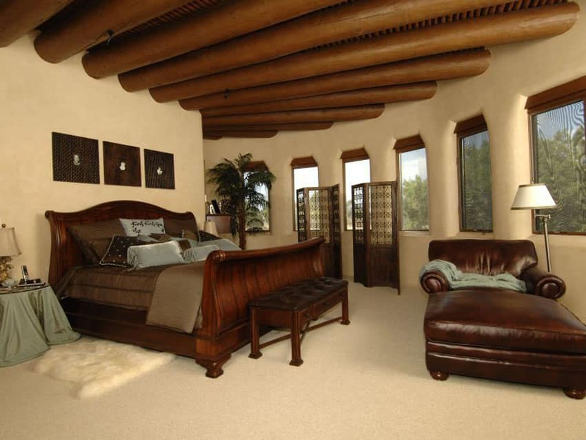Tan Mediterranean style bedroom with round exposed beam ceiling