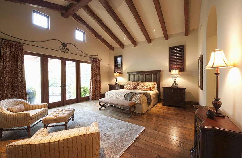 Tan painted bedroom with vaulted ceiling and exposed beams