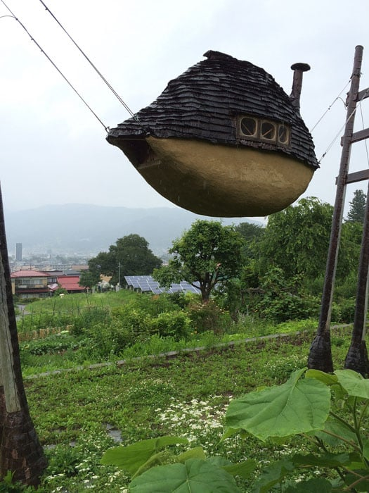 Tiny floating house suspended by wires