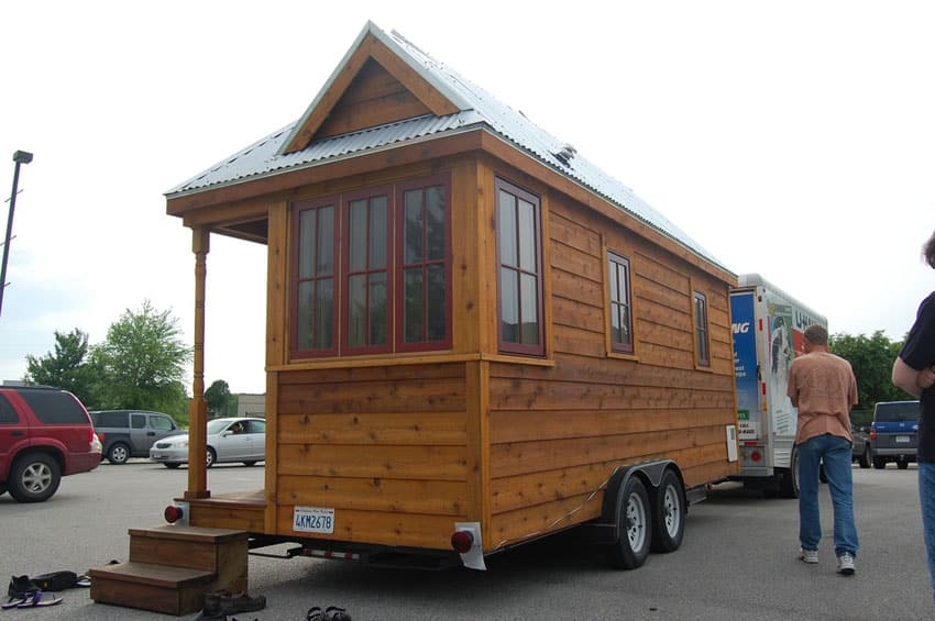 Tiny house on wheels being towed by truck