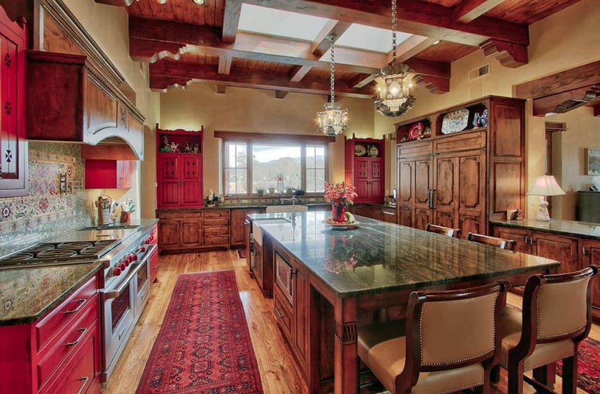 Traditional kitchen with red cabinets, light wood floors and large island with granite countertops