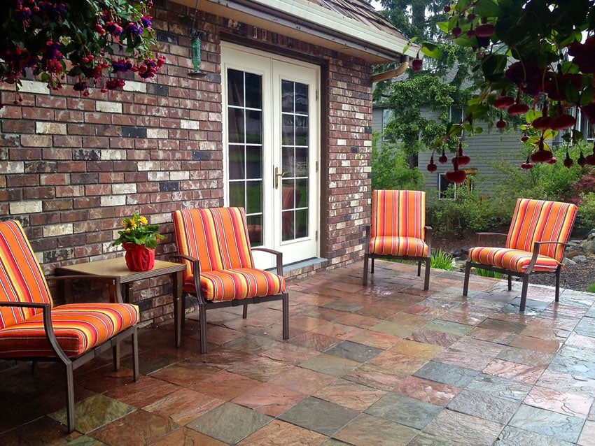 Traditional slate stone patio behind brick home