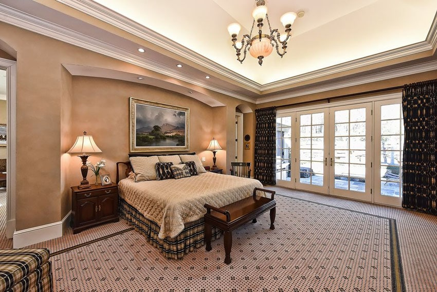 Traditional tan bedroom with tray ceiling and wall alcove for bed