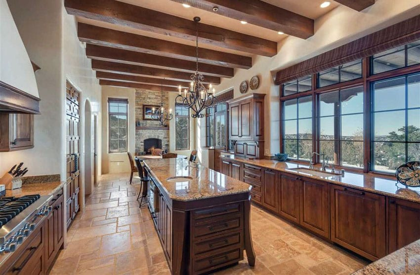Tuscan kitchen with gold granite counters narrow island and travertine flooring