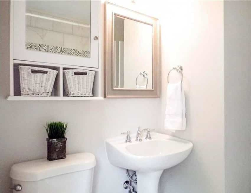 White bathroom with medicine cabinet with wicker baskets