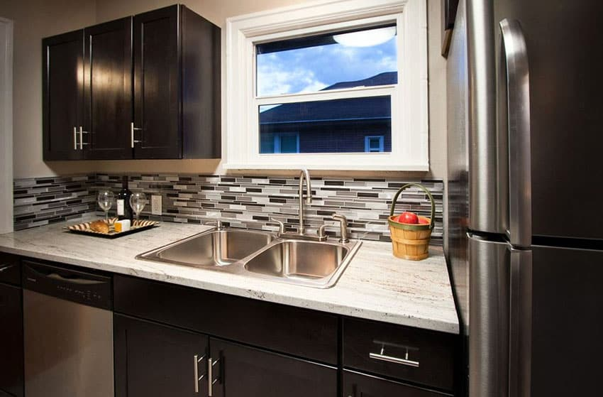 Compact contemporary kitchen with dark cabinets, light granite counter and black and white tile backsplash
