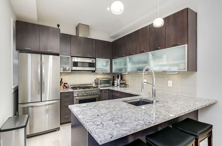 Contemporary u shaped kitchen with quartz countertop and dark cabinets with frosted glass doors