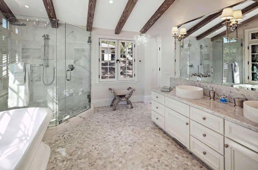 Luxury bathroom with exposed beam ceiling, stone pebble floors, soaking tub and vessel sinks