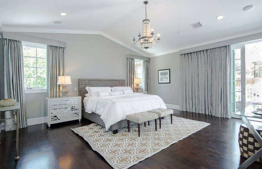 Master bedroom with silver wall covering and decor with walnut floors
