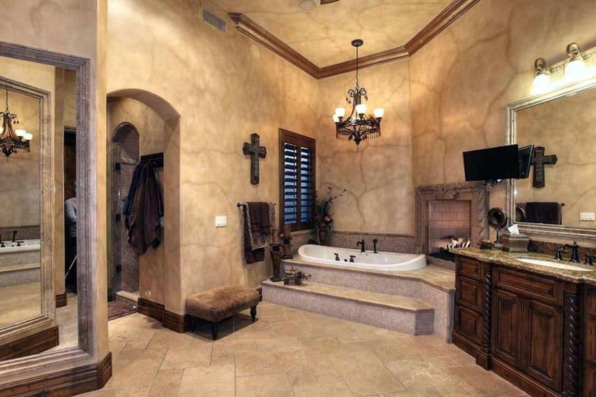 Mediterranean style luxury bathroom with enclosed tub, fireplace, dark wood vanity and limestone floors