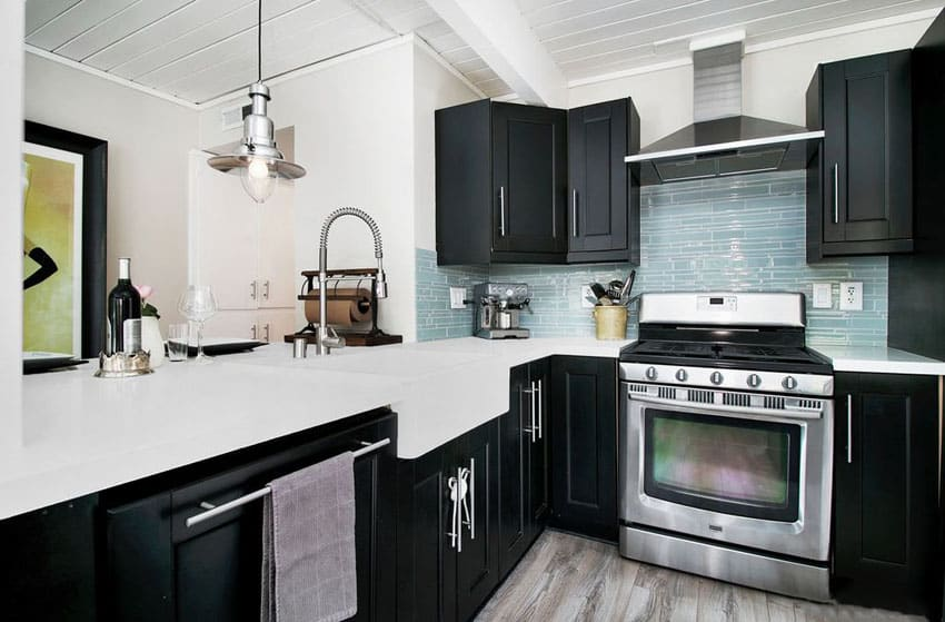 Small kitchen with black cabinets, arctic white cabinets and blue glass backsplash