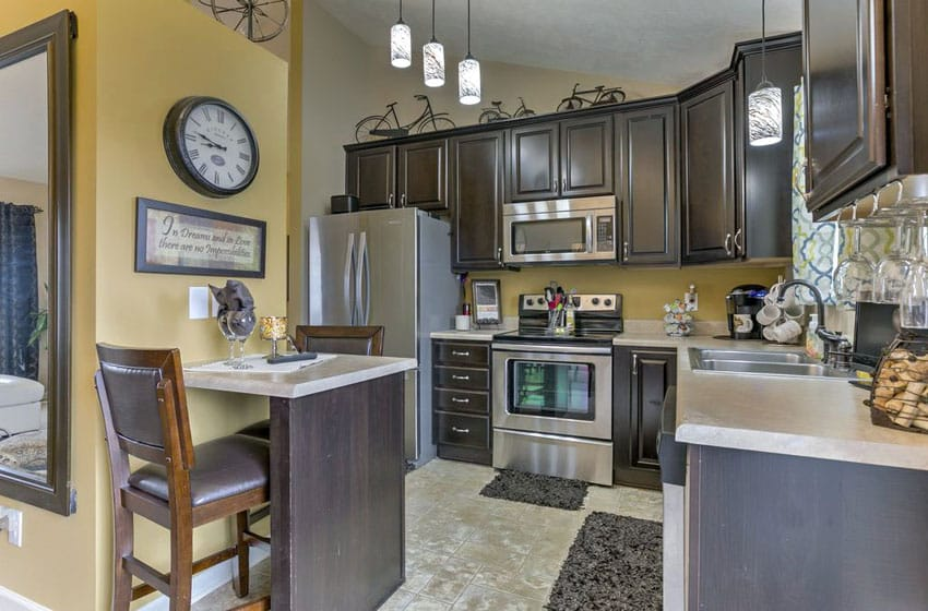 Small traditional kitchen with dark raised panel cabinets and one person dining peninsula