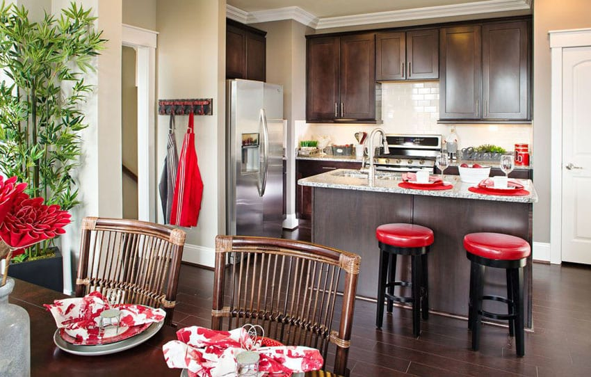 Small traditional kitchen with island dark cabinets, light granite counters and red bar stools