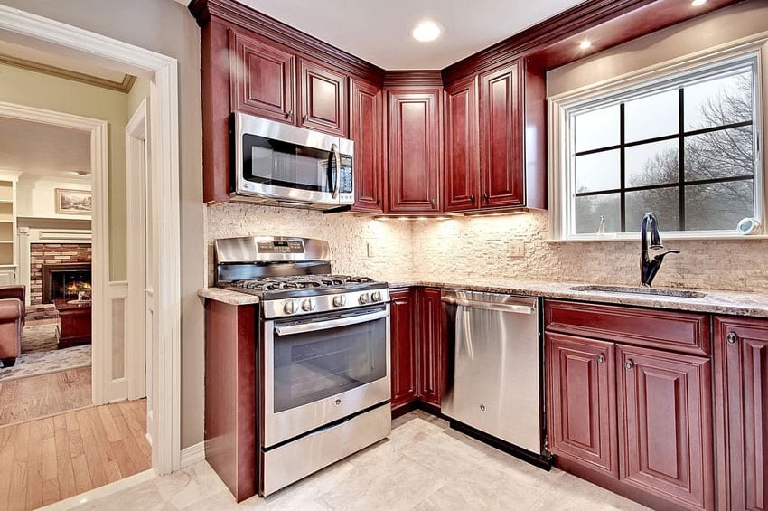 Small traditional l shaped style kitchen with dark red cabinets and stone backsplash