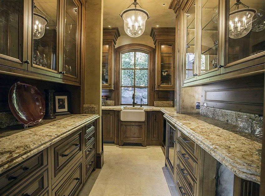 Traditional kitchen with custom wood cabinets, cream granite counters and travertine floors
