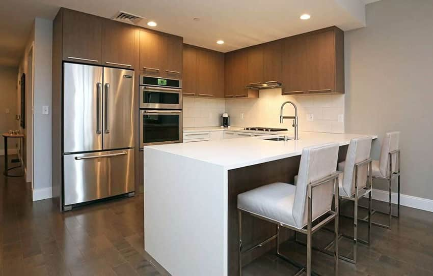 U shaped contemporary kitchen with brown cabinets, arctic white countertop and dining peninsula