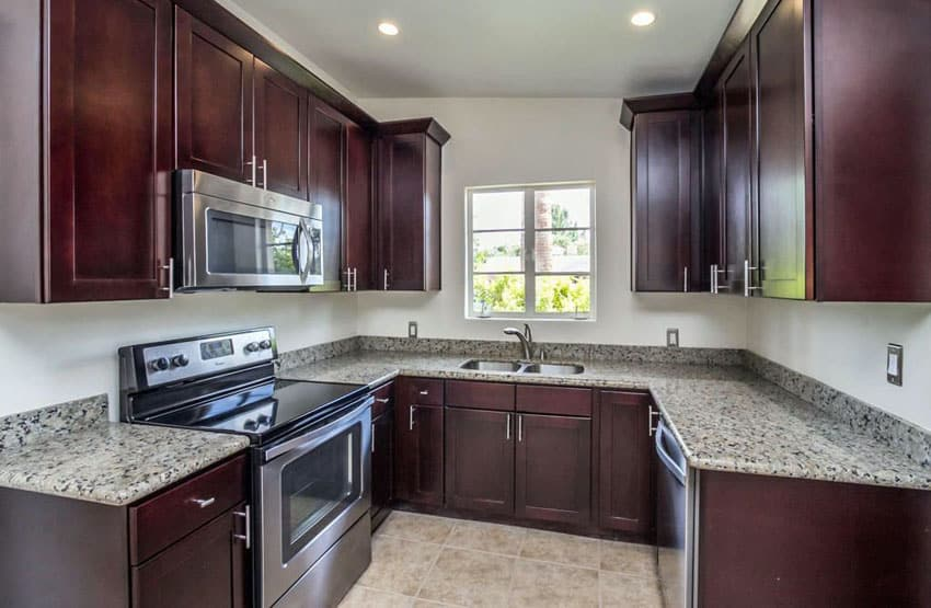 U shaped kitchen with dark shaker cabinets and granite counters