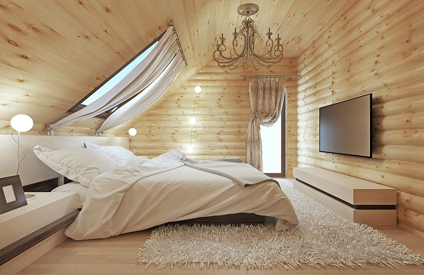 Wood walled loft bedroom with skylight above bed
