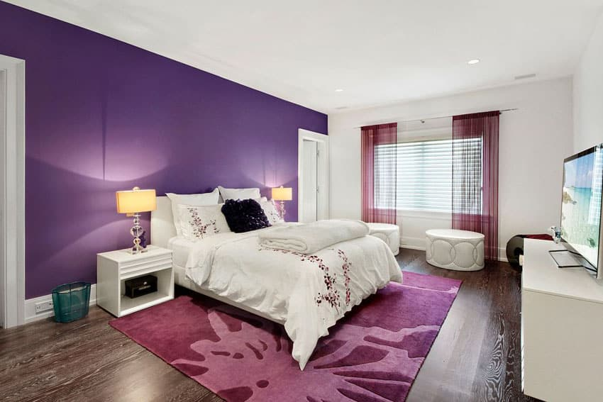 Bedroom with bold purple accent wall and white paint with white furniture