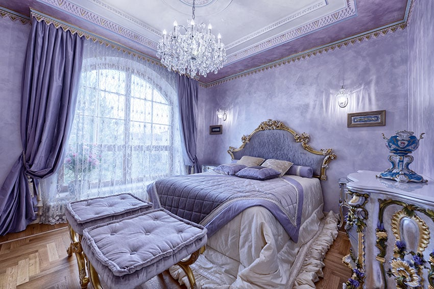 Luxury french inspired purple bedroom with gold gilded furniture and crystal chandelier