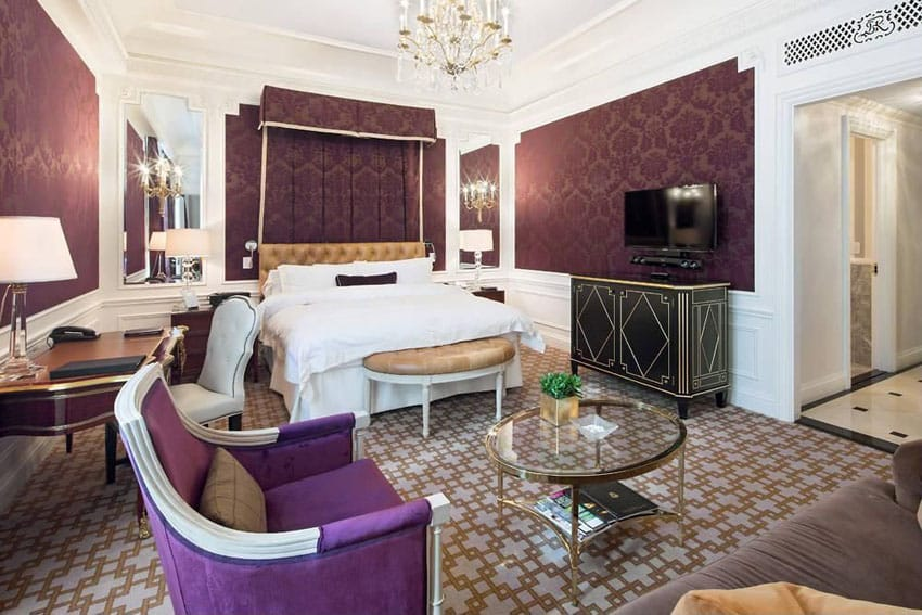 Master bedroom with purple textured walls decor and gold chandelier