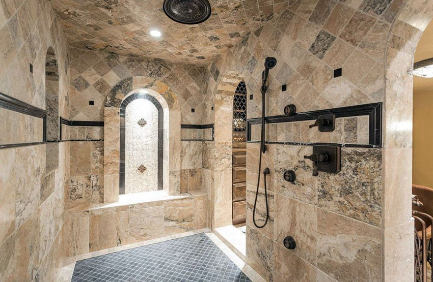 Mediterranean shower with travertine tile walls and marble floor tile with bronzed hardware and rainfall showerhead
