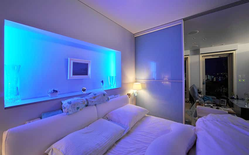 Modern bedroom with purple walls mood lighting from wall alcove and white furnishings