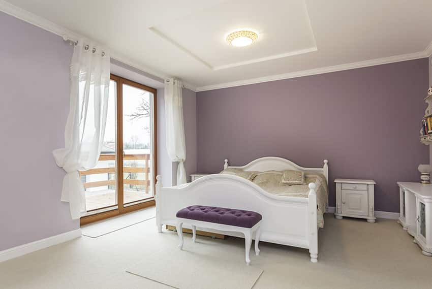 White and purple themed bedroom with white furniture and balcony
