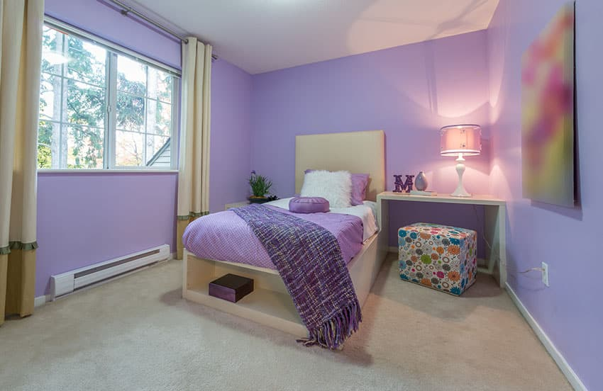 Purple painted girls bedroom with cream color bed frame curtains and end table